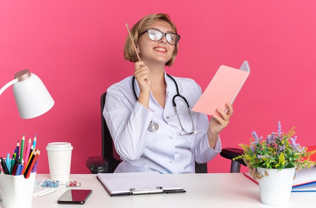 Impressionato giovane dottoressa che indossa abito medico con stetoscopio e occhiali si siede alla scrivania con strumenti medici che tengono il taccuino con la matita isolata sulla parete rosa