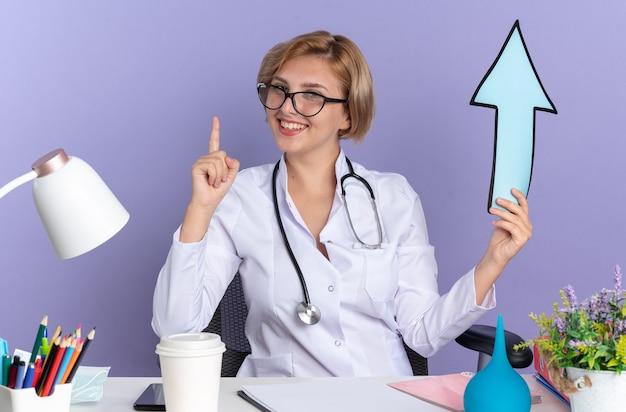 Impressionato giovane dottoressa che indossa abito medico con stetoscopio e occhiali si siede al tavolo con strumenti medici che tengono i punti del segno di direzione in alto isolato sulla parete blu