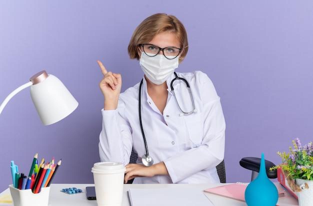 Impressionato giovane dottoressa che indossa abito medico con stetoscopio e occhiali con maschera medica si siede al tavolo con strumenti medici punta in alto isolato sulla parete blu