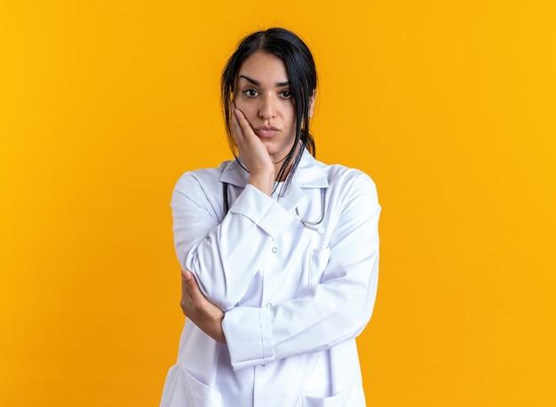 黄色の壁に分離された頬に手を置く聴診器で医療ローブを着ている感動若い女性医師