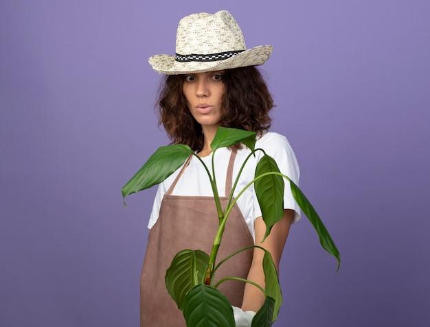 植物を保持している園芸帽子を身に着けている制服を着た若い女性の庭師に感銘を受けました