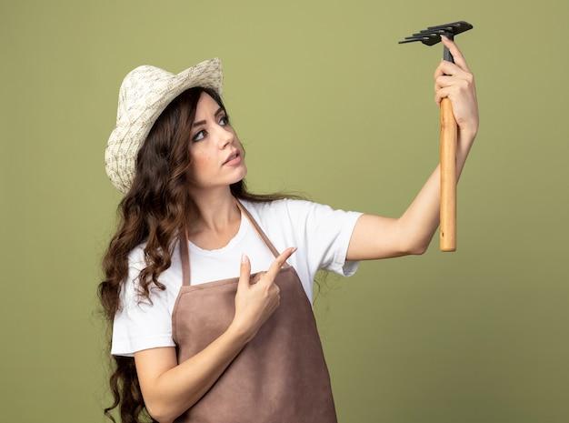 Впечатленная молодая женщина-садовник в униформе в садовой шляпе держит и указывает на грабли, изолированные на оливково-зеленой стене