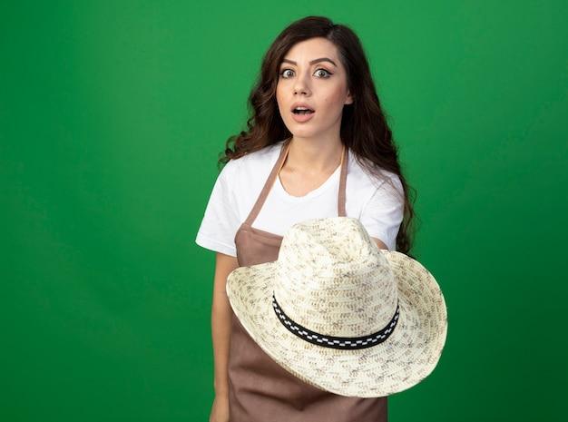 Giardiniere femminile giovane impressionato in cappello di giardinaggio della holding uniforme isolato sulla parete verde