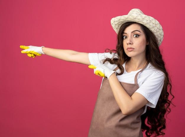 Impressionato giovane giardiniere femminile in uniforme indossando guanti e cappello da giardinaggio punti a lato isolato sulla parete rosa