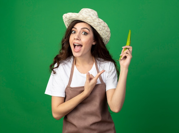 Il giovane giardiniere femminile colpito in uniforme che porta il cappello da giardinaggio tiene e indica il peperoncino isolato sulla parete verde