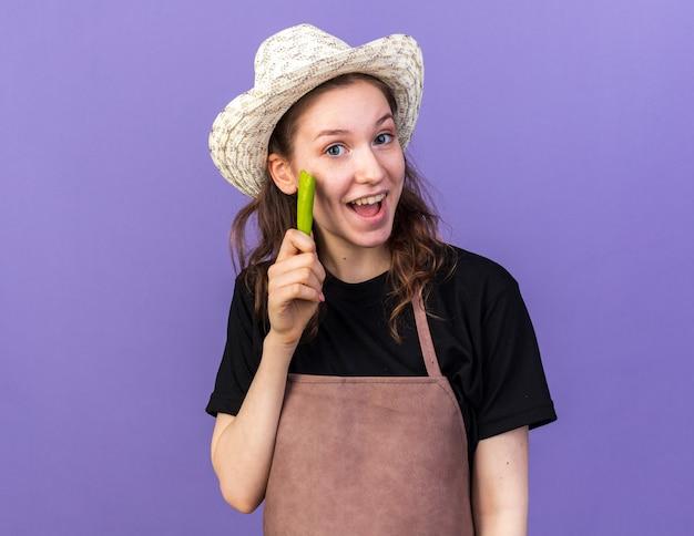 Впечатленная молодая женщина-садовник в садовой шляпе с перцем