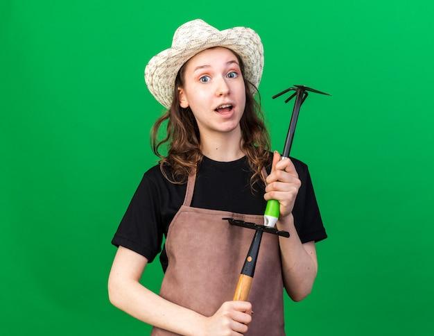 Впечатленная молодая женщина-садовник в садовой шляпе, держащая грабли с граблями для мотыги