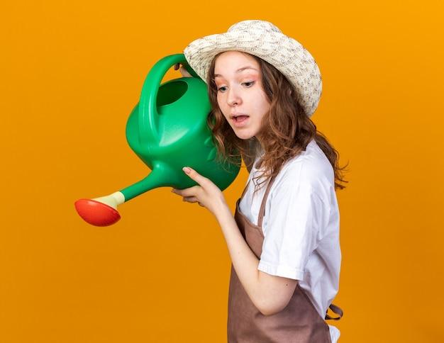 Impressionato giovane giardiniere femminile che indossa cappello da giardinaggio che innaffia con annaffiatoio isolato su parete arancione