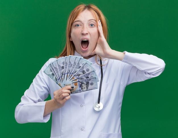 의료 가운과 청진기를 입은 젊은 여성 진저 의사는 녹색 벽에 격리된 비명을 지르는 정면을 바라보며 돈을 만지는 얼굴을 하고 있다