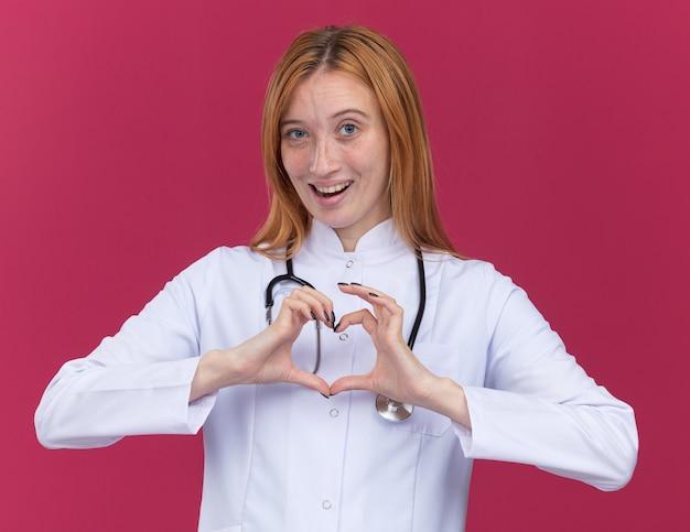 Impressionato giovane dottoressa allo zenzero che indossa una tunica medica e uno stetoscopio guardando la parte anteriore facendo il segno del cuore isolato sul muro cremisi