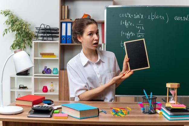 Impressionato giovane insegnante di matematica femminile seduto alla scrivania con materiale scolastico tenendo e indicando la mini lavagna guardando davanti in classe