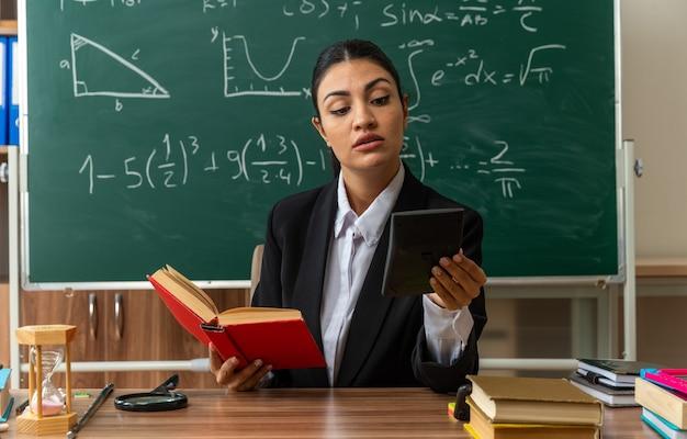Una giovane insegnante impressionata si siede al tavolo con materiale scolastico tenendo in mano un libro e guardando la calcolatrice in mano in classe