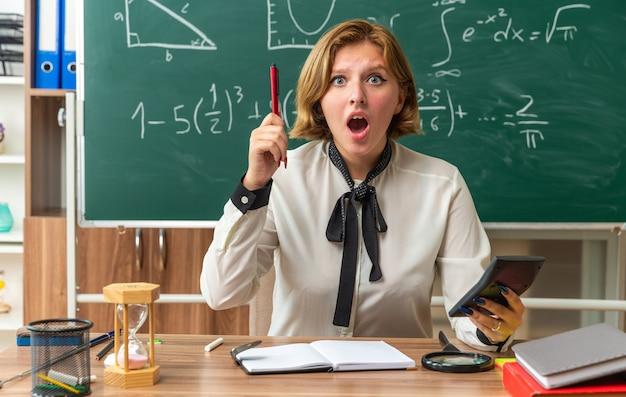 Impressionato giovane insegnante femminile si siede al tavolo con materiale scolastico tenendo la penna con la calcolatrice in classe