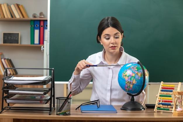 Impressionata giovane insegnante seduta a tavola con gli strumenti della scuola che tiene e mette il puntatore sul globo in classe