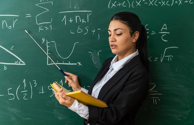 Impressionato giovane insegnante di sesso femminile in piedi davanti alla lavagna libro di lettura tenendo il puntatore stick in classe