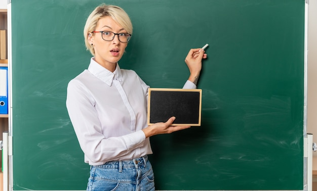 Impressed young female teacher wearing glasses in classroom standing in profile view in front of chalkboard