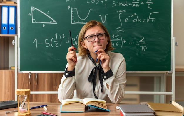 안경을 쓰고 감동적인 젊은 여성 교사는 교실에서 연필을 잡고 학교 도구로 테이블에 앉아있다.