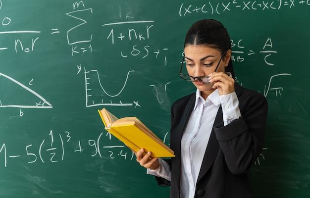 Impressionato giovane insegnante di sesso femminile con gli occhiali in piedi davanti alla lavagna leggendo il libro in classe