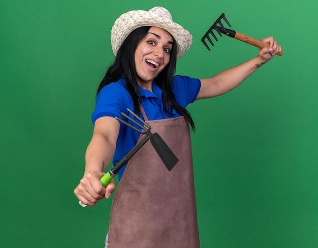 Impressionato la giovane ragazza giardiniere che indossa l'uniforme e il cappello alzando il rastrello e allungando il rastrello della zappa verso la parte anteriore guardando la parte anteriore isolata sulla parete verde