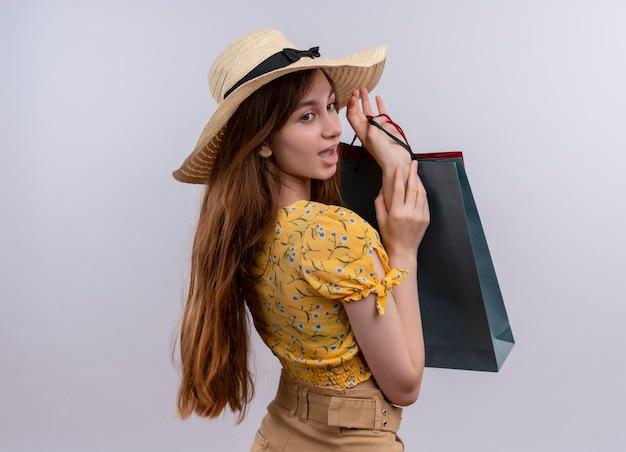 Ragazza colpita che tiene i sacchetti di carta che mette la mano su un altro che esamina il lato sullo spazio bianco isolato con lo spazio della copia