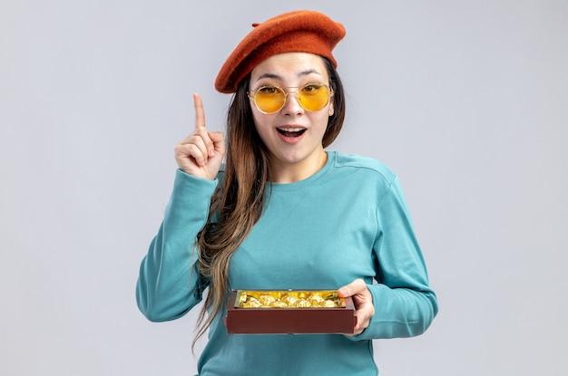 La ragazza impressionata il giorno di san valentino indossa un cappello con gli occhiali che tiene una scatola di caramelle punta verso l'alto isolato su sfondo bianco
