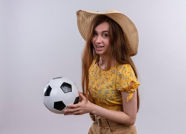 Cappello da portare impressionato della ragazza che tiene il pallone da calcio su spazio bianco isolato
