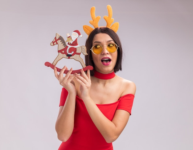 Impressed young girl wearing reindeer antlers headband and glasses holding and looking at santa on rocking horse figurine isolated on white background with copy space