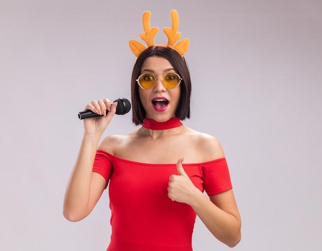 Impressionato giovane ragazza che indossa corna di renna archetto e occhiali tenendo il microfono guardando la telecamera che mostra il pollice in alto isolato su sfondo bianco