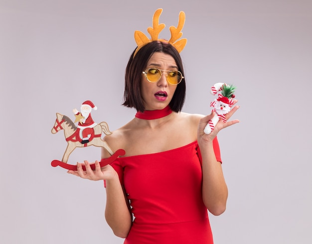 Impressed young girl wearing reindeer antlers headband and glasses holding santa on rocking horse figurine and candy cane ornament looking at candy cane ornament isolated on white background