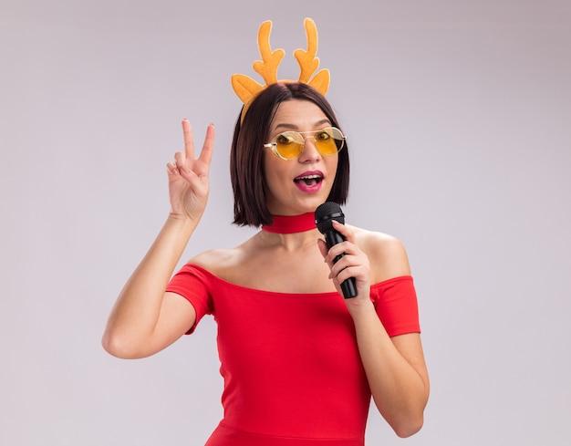 Impressionato giovane ragazza che indossa corna di renna archetto e occhiali parlando nel microfono guardando la telecamera facendo segno di pace isolati su sfondo bianco