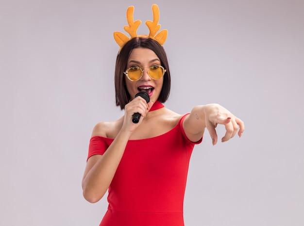 Impressionato giovane ragazza che indossa corna di renna archetto e occhiali parlando nel microfono guardando e puntando a lato isolato su sfondo bianco