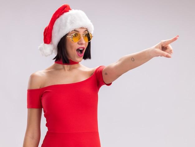 산타 모자와 안경을 찾고 흰색 배경에 고립 된 측면에서 가리키는 감동 어린 소녀