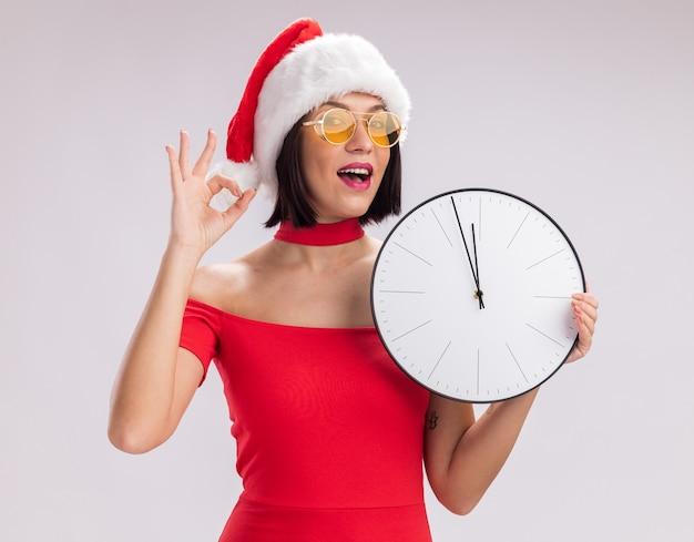 Ragazza impressionata che indossa cappello e occhiali da babbo natale che tengono l'orologio guardando la telecamera facendo segno ok isolato su sfondo bianco