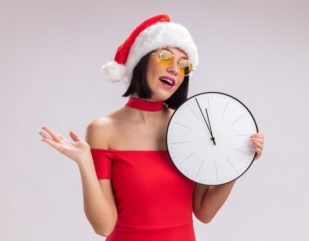Ragazza impressionata che indossa cappello da babbo natale e occhiali che tengono l'orologio guardando la telecamera che mostra la mano vuota isolata su sfondo bianco
