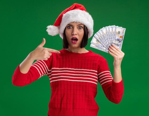 산타 모자를 쓰고 녹색 배경에 고립 된 카메라를보고 돈을 가리키는 감동 어린 소녀