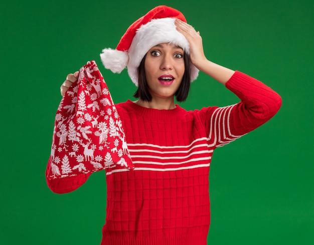 緑の壁に隔離された頭に手を置いてクリスマスプレゼント袋を保持しているサンタの帽子をかぶって感動の少女