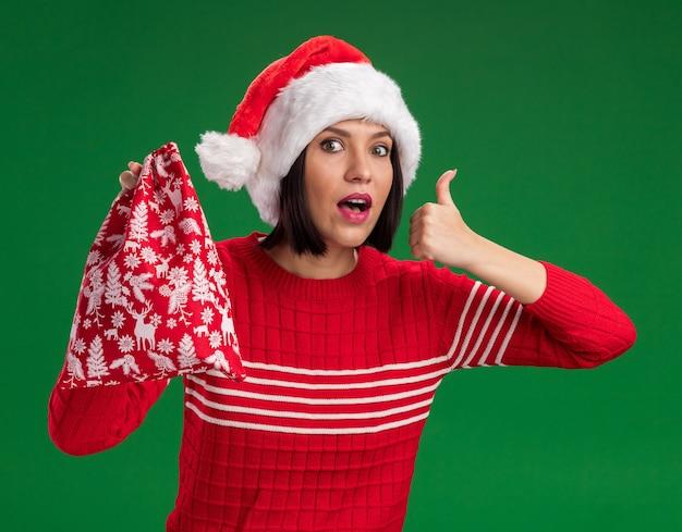 크리스마스 선물 자루를 들고 산타 모자를 쓰고 감동 어린 소녀는 녹색 배경에 고립 엄지 손가락을 보여주는 카메라를보고