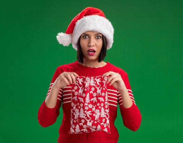 크리스마스 선물 자루를 들고 산타 모자를 쓰고 감동 어린 소녀 녹색 배경에 고립 된 카메라를보고 열기