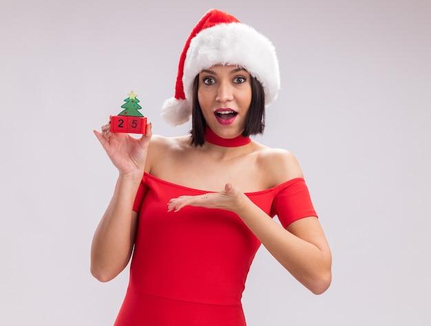 Ragazza impressionata che indossa il cappello di santa che tiene il giocattolo dell'albero di natale con la data che lo punta guardando la telecamera isolata su sfondo bianco