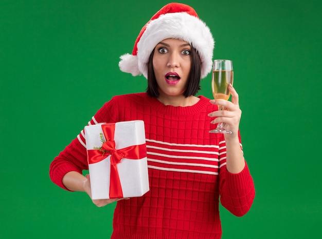 Впечатленная молодая девушка в шляпе санта-клауса, держащая подарочную упаковку и бокал шампанского, изолированную на зеленой стене
