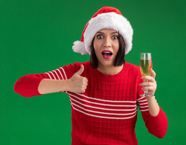 Ragazza colpita che porta il cappello della santa che tiene il bicchiere di champagne che mostra il pollice in su isolato sulla parete verde