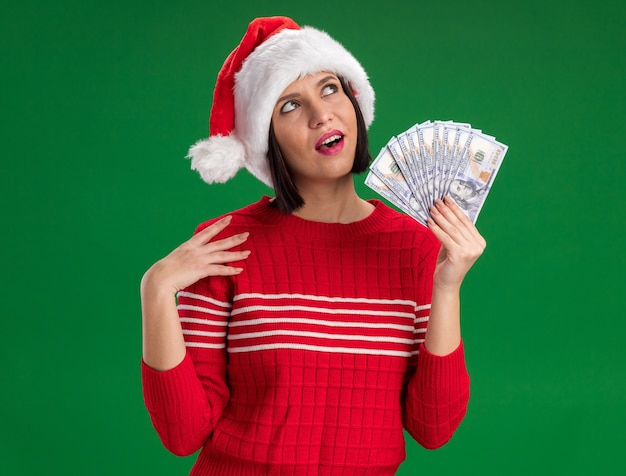 Impressed young girl wearing santa hat holding money touching shoulder looking up isolated on green wall