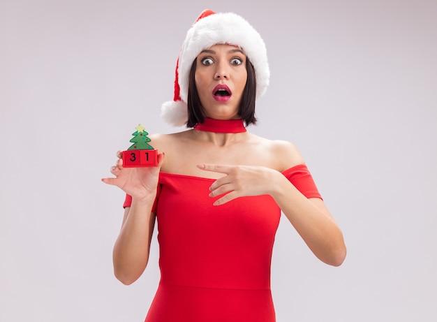 Ragazza impressionata che indossa il cappello di babbo natale che tiene e indica il giocattolo dell'albero di natale con la data che guarda l'obbiettivo isolato su sfondo bianco