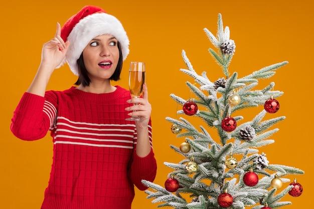 Впечатленная молодая девушка в шляпе санта-клауса, стоящая возле украшенной елки с бокалом шампанского, глядя в сторону, указывающую вверх, изолированную на оранжевом фоне