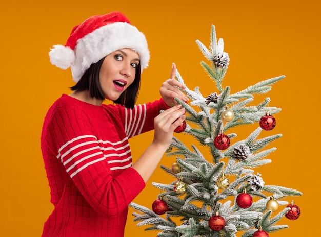 Impressionato giovane ragazza che indossa il cappello della santa in piedi in vista di profilo vicino all'albero di natale decorarlo con palline di natale guardando la telecamera isolata su sfondo arancione