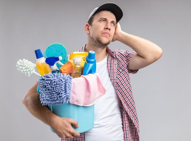 Impressionato giovane ragazzo pulitore che indossa il cappello che tiene il secchio con strumenti di pulizia che mettono la mano sulla guancia isolata su sfondo bianco
