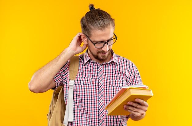 Impressionato giovane studente che indossa uno zaino con gli occhiali che tiene e guarda il libro che graffia la testa isolata sul muro arancione