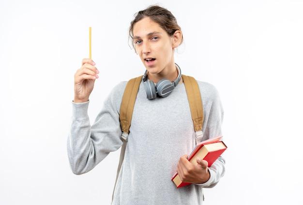 白い壁に隔離されたペンを上げる本を保持している首にヘッドフォンでバックパックを身に着けている感動の若い男の学生