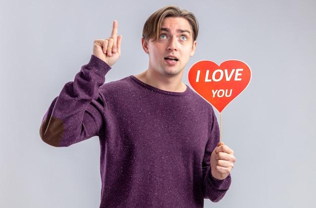 Impressionato giovane ragazzo il giorno di san valentino che tiene il cuore rosso su un bastone con ti amo il testo punta verso l'alto isolato su sfondo bianco