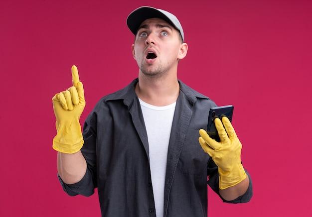 印象深刻的年轻hamdsome清洁家伙穿着t恤和帽子和手套拿着电话点孤立在粉红色的墙壁上